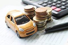 微型汽车模型、硬币堆、计算器和储蓄存款书或者财政决算在书桌桌上 免版税库存图片
