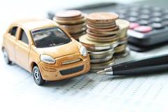 微型汽车模型、硬币堆、计算器和储蓄存款书或者财政决算在书桌桌上 图库摄影