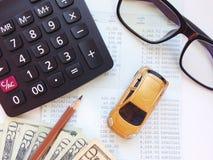 微型汽车模型、计算器、美元金钱和储蓄存款书或者财政决算在办公室桌上 免版税库存照片