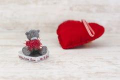 微型玩具熊和红色心脏在木背景 免版税库存图片