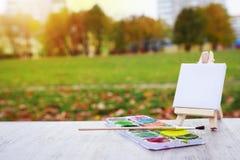 微型画架、油漆和刷子在城市的背景停放 在城市公园画一个风景 艺术家和绘画概念 库存照片