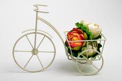 微型白色三轮车花盆和有些花 免版税库存图片
