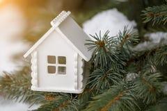 微型白色房子在一个杉木分支在冬天 免版税库存照片