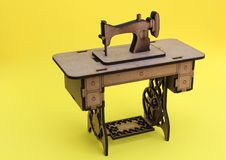 微型缝纫机,由木头制成,在黄色背景 免版税库存照片