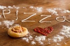 微型薄饼用香肠和乳酪在木桌上 免版税库存照片