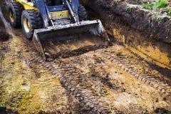 微型装载者部份看法在站立在坑的泥的在挖掘工作期间 免版税库存图片