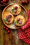 微型馅饼用新鲜的樱桃和香草乳蛋糕和焦糖,在一张木桌上的可口点心 免版税库存图片