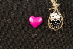 微型头骨头和桃红色心脏 库存照片