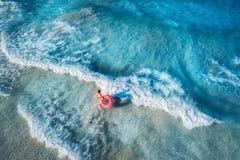 微小的少妇游泳鸟瞰图在多福饼游泳圆环的 免版税库存图片