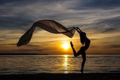 微小的性感的女孩跳舞剪影与围巾的在海滩 免版税库存图片