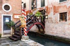 微小的桥梁看法有花和路灯柱的到一家典型的威尼斯餐馆里 库存照片