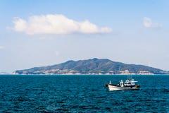 微小的海岛和渔夫小船 免版税库存照片