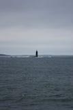 微小的灯塔在浩大的海洋(纵向) 免版税图库摄影