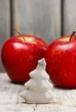 微小的陶瓷圣诞树和大红色苹果 免版税库存图片