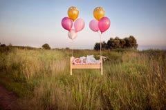 微小的婴孩睡着在他的在鞋带帽子A的小儿床在盖帽和飞行与气球 免版税图库摄影