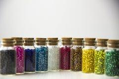 微小的玻璃瓶充满小珠 免版税库存照片