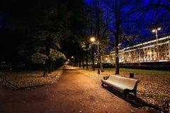 微明的城市公园与长凳、路、胡同和树秋天 秋天夜公园 免版税库存图片