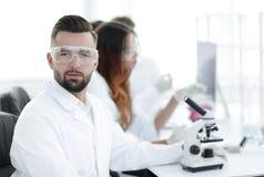 微生物学家和他的同事在一个现代实验室坐 免版税库存照片