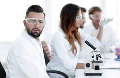 微生物学家和他的同事在一个现代实验室坐 免版税库存图片