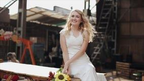 微笑一个年轻俏丽的新娘的画象坐和户外 慢的行动 股票录像
