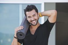 微笑一个的人的纵向拿着瑜伽席子 图库摄影