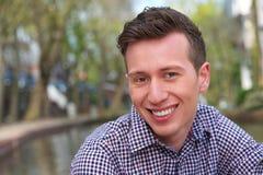 微笑一个英俊的年轻的人的水平的画象户外 库存照片