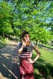 微笑一名年轻美丽的妇女的画象支持绿色树在公园 免版税图库摄影