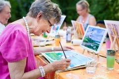 微笑一名愉快的资深的妇女的侧视图,当画作为消遣活动或疗法户外与小组一起时 免版税库存照片