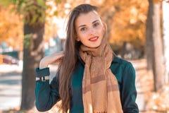 微笑一条长的围巾的年轻逗人喜爱的女孩直接地看和 图库摄影