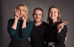 微笑三个年轻的朋友一起站立,拥抱,笑和 在灰色墙壁射击的演播室 库存照片