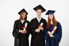 微笑三个愉快的毕业生拿着看在白色背景的文凭照相机 免版税库存照片