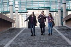 微笑三名的学生走和 库存图片