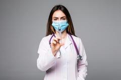 微笑与一个注射器的一位年轻女性医生的画象在她的手上 一位美丽的妇女医生的画象灰色的 图库摄影