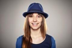 微笑与一个蓝色帽子的一个正常女孩的画象 库存图片
