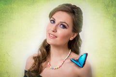 微笑与一只蓝色蝴蝶的一名白肤金发的妇女的春天概念 免版税库存照片