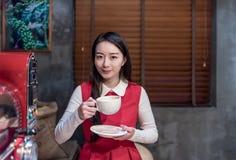 微笑与一杯咖啡的美丽的亚裔妇女 免版税库存图片