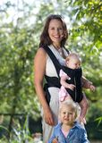 微笑与两个小女儿的美丽的母亲 库存照片