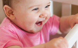 微笑与两颗更低的牙的新出生的女婴 免版税库存图片