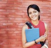 微笑与书的愉快的印第安学员。 图库摄影