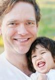 微笑与他的男婴的英俊的父亲 库存图片