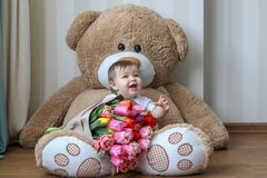 微笑与他的第一颗牙的逗人喜爱的矮小的婴孩,坐与郁金香大花束的巨大的玩具熊  库存照片