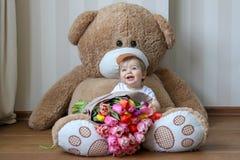 微笑与他的第一颗牙的逗人喜爱的矮小的婴孩,坐与郁金香大花束的巨大的玩具熊  免版税库存图片