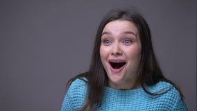 微笑与兴奋的年轻俏丽的深色的女性特写镜头射击看照相机有在灰色隔绝的背景 股票视频