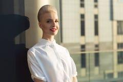 微笑与在城市都市室外背景后的白肤金发的莫霍克族的成功的女商人画象  图库摄影