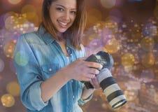 微笑与在手上的照相机的摄影师妇女在阳台上 城市夜点燃并且飘动 图库摄影