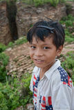 微笑与在摆在2015年8月01日的面孔的thanaka浆糊的未认出的缅甸孩子在M 库存图片