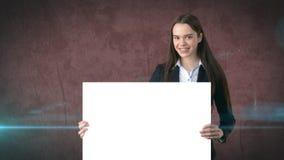 微笑与在褐色被隔绝的空白的白板的女商人画象 与长的头发的女性模型 免版税图库摄影