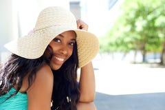 微笑与太阳帽子的愉快的年轻黑人妇女户外 免版税库存照片