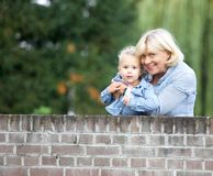 微笑与女婴的祖母户外 免版税库存照片