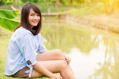 微笑与完善的微笑和白色牙在公园和看照相机的妇女 免版税库存图片
